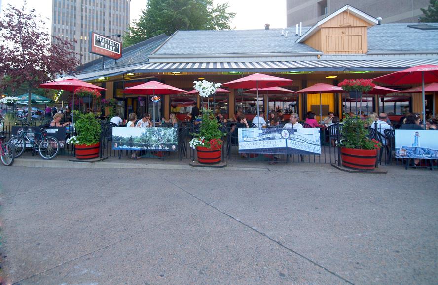 People enjoying open air dining at sidewalk cafes.